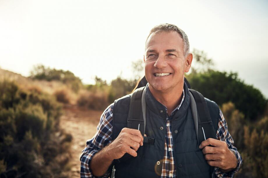 smiling man hiking with backpack