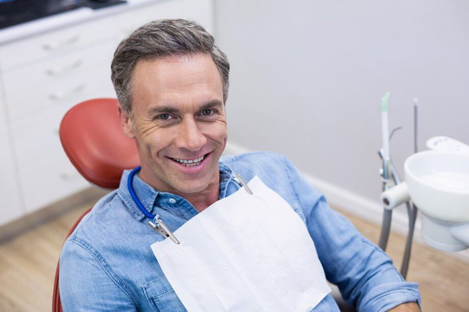smiling male patient in dental chair