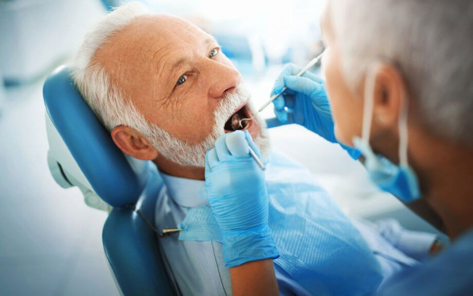 older man getting examined by dentist